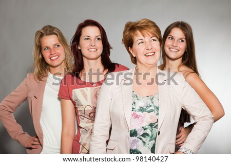 Happy family of mother with three daughters isolated on grey background. Fashion style studio portrait. - stock photo