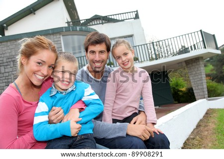 Happy family of 4 people sitting in front of new home - stock photo