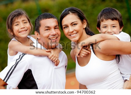Happy family of tennis players at the court - stock photo
