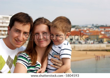Happy family of three at European destination. Typical Mediterranean small town with orange roofs visible on background - stock photo