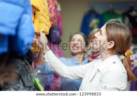 Happy family of three generations chooses winter wear at clothes store - stock photo