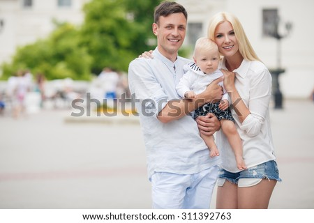 happy family of three having fun and smiling outdoor. Happy young family spending time together outside. Happy mother, father and son - stock photo