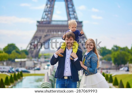 Happy family of three having fun together in Paris near the Eiffel tower - stock photo
