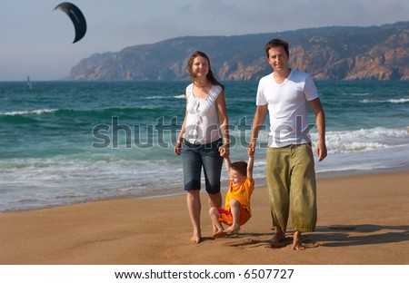 Happy family of three having fun walking along the beach - stock photo