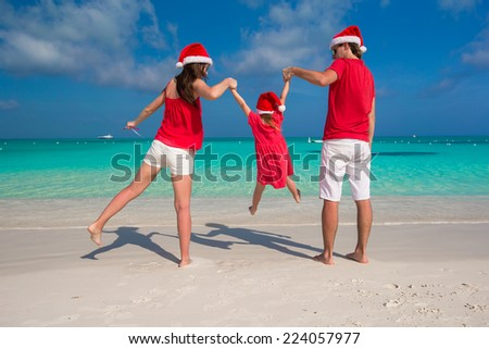 Happy family of three in Christmas Hats during tropical vacation - stock photo