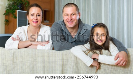 Happy family of three in domestic interior - stock photo