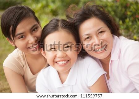 Happy family of three looking at camera outdoors - stock photo