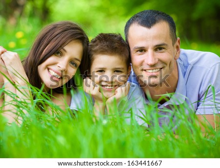 Happy family of three lying on grass. Concept of happy family relations and carefree leisure time - stock photo