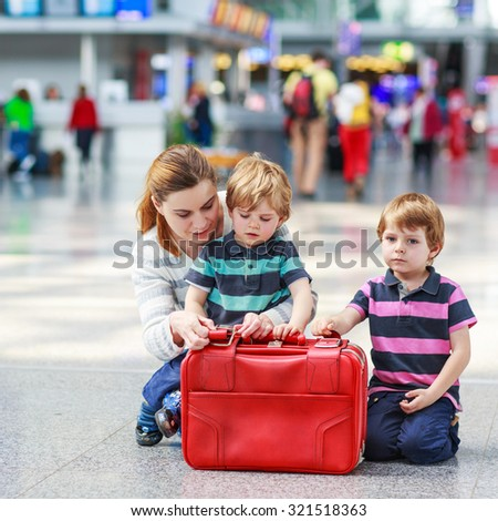 Happy family of three: Mother and two little sibling boys at the airport, traveling together. - stock photo