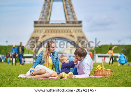 Happy family of three, mother, father and little toddler boy, having picnic in Paris near the Eiffel tower - stock photo