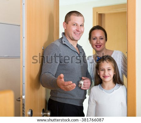 Happy family of three opening door of new apartment  - stock photo