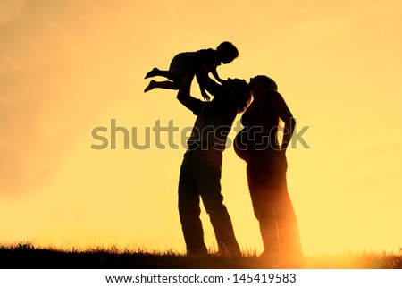 happy family of three people, including a pregnant mother, a father, and a toddler celebrate outside at Sunset, Silhouette against the evening sky - stock photo