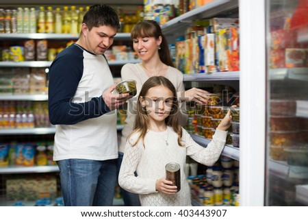 Happy family of three purchasing canned food at supermarket. Focus on girl  - stock photo