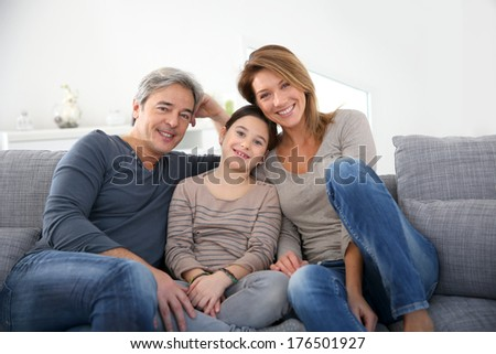 Happy family of three relaxing in sofa - stock photo