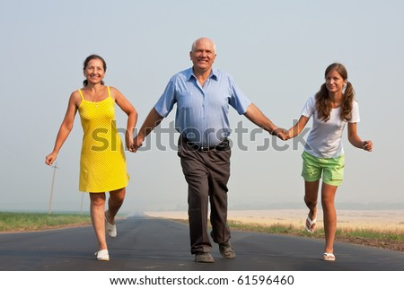 Happy family of three run over a  road at summer - stock photo