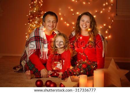 Happy family of three smiling at Christmas Eve at home - stock photo