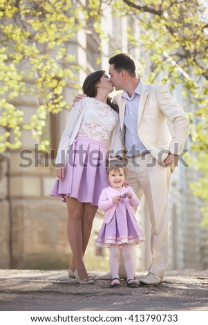 Happy family of three spending their family time together on the street, father kisses  mother and their daughter laughs - stock photo