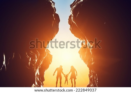 Happy family of three standing in between two rocky mountains at the entrance of a new better world or life sybmolized by bright shining sun. Unique concept of hope, positive future. - stock photo