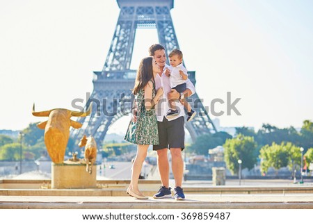 Happy family of three standing in front of the Eiffel tower and enjoying their vacation in Paris, France - stock photo
