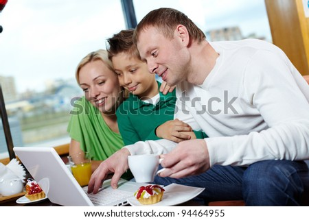 Happy family of three using a laptop while being at a cafe - stock photo