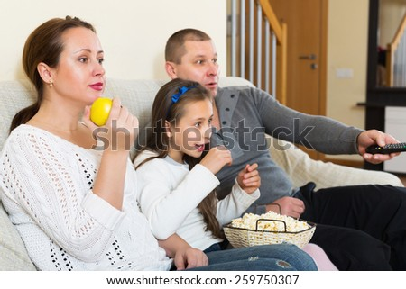 Happy family of three watching movie in domestic interior. Focus on woman - stock photo