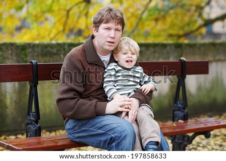 Happy family of two: Adorable little toddler boy and his father sitting on bench in autumn city - stock photo