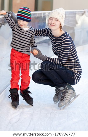 happy family of two enjoying ice skating at winter  - stock photo