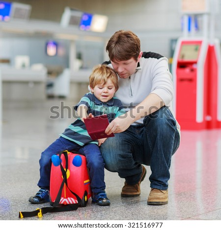 Happy family of two: Father and little son at the airport, traveling together and holding passport in hand. - stock photo