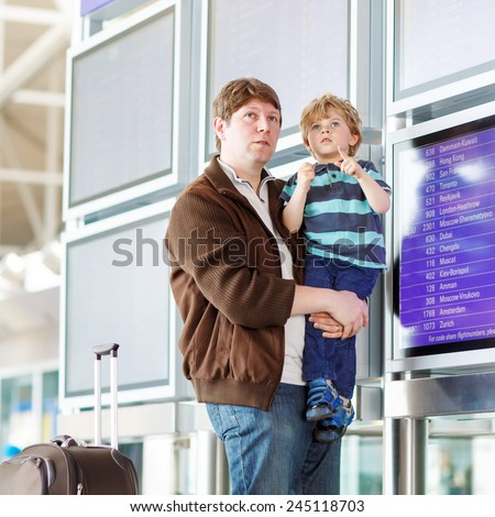 Happy family of two: Father and little son at the international airport, looking on flight board at terminal, going on vacation. Ready for take off. - stock photo