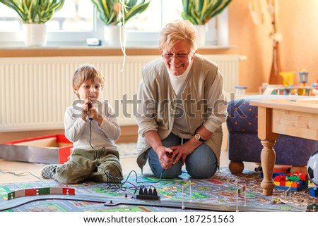 Happy family of two: Grandmother and little grandson playing with racing cars on racetrack, indoors, together. Selective focus on senior woman. - stock photo