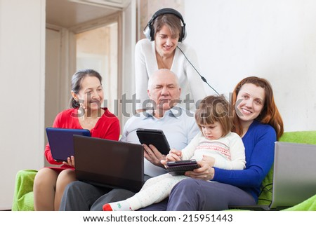 Happy family of with various portable computers on sofa - stock photo