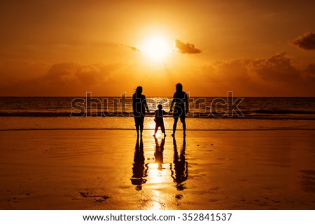 Happy family on a beach at sunrise with child mother and father - stock photo