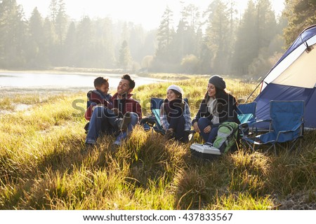 Happy family on a camping trip relaxing by their tent - stock photo