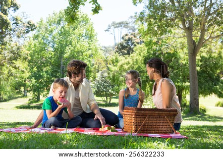 Happy family on a picnic in the park on a sunny day - stock photo
