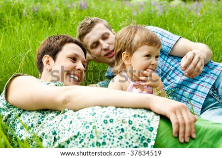Happy family on a summer meadow - stock photo