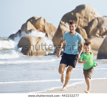 happy family on beach playing, father with son walking sea coast - stock photo