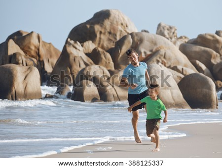happy family on beach playing, father with son walking sea coast, rocks behind smiling enjoy summer - stock photo