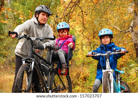 Happy family on bikes in autumn park, having fun, sport and cycling with kids  - stock photo