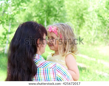 happy family on nature outdoors mother playing with her  little daughter on nature     - stock photo