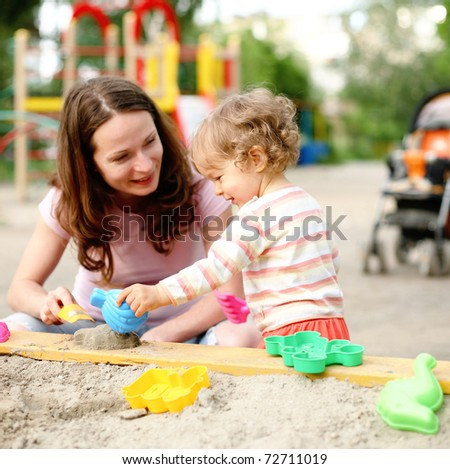 Happy family on playground in summer - stock photo