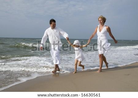Happy family on the beach - stock photo
