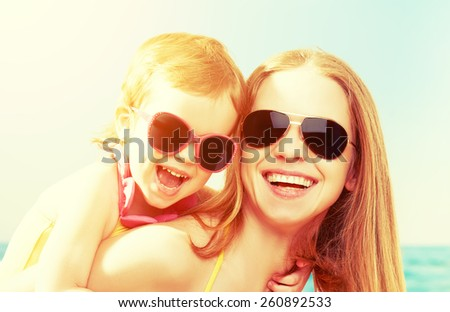 happy family on the beach. mother and baby daughter  at sea - stock photo