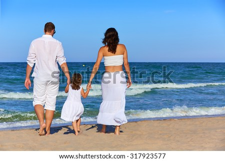 Happy family on the beach sand walking rear back view in summer - stock photo
