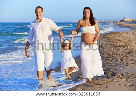 Happy family on the beach sand walking with pregnant mother woman - stock photo