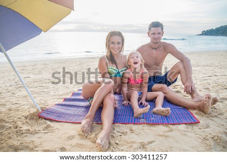 Happy family on the beach smiling and looking at camera - Tourists on vacation on a tropical island  - stock photo