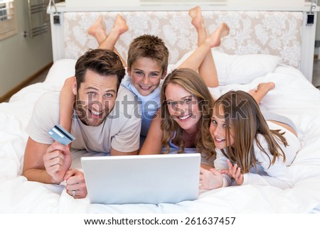 Happy family on the bed using laptop at home in bedroom - stock photo