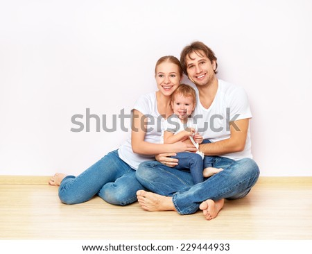 Happy family on the floor near the empty blank  wall in the apartment bought on mortgage - stock photo