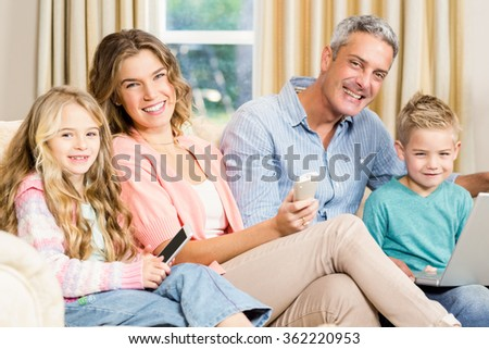 Happy family on the sofa looking at the camera - stock photo