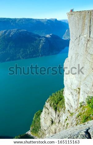 Happy family on top of Preikestolen massive cliff (Norway, Lysefjorden summer view) - stock photo