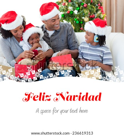Happy family opening Christmas presents against feliz navidad - stock photo